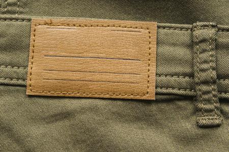 khaki pants: Blank leather label on khaki cloth as a background