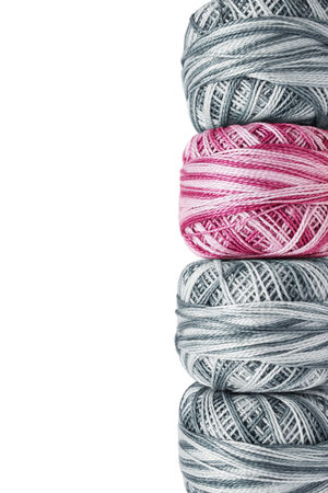 Pink yarn among gray bobbins over white as a background photo