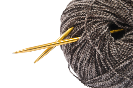 Golden knitting needles in a ball of melange yarn closeup over white photo