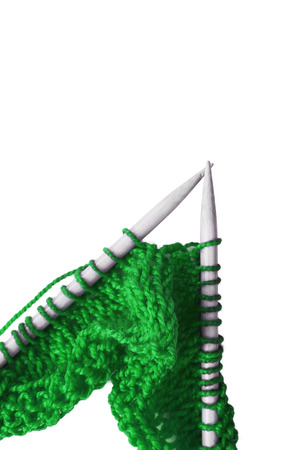 brigth: Brigth green knitting on wooden needles on white background