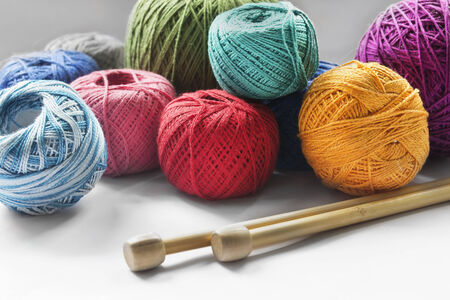 Group of various yarn balls and knitting needles closeup photo