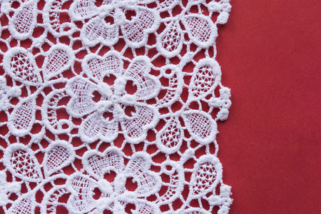 Vintage white lace over red as a background photo
