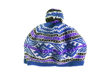 Knitted ornamental blue cap with pompon isolated over white photo