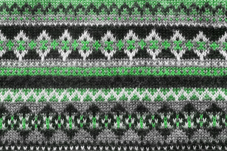 Ornamental green and black knitting closeup as a background photo