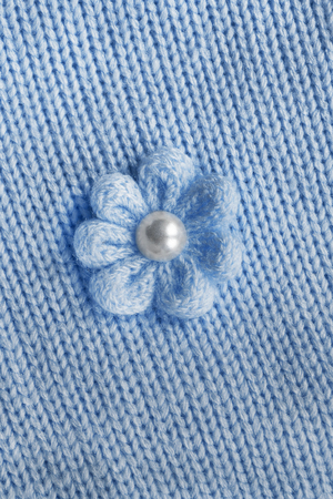 Knitted flower on blue knitted cloth as a background photo