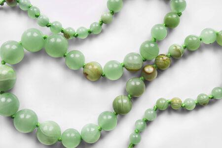 nephritis: String of nephrite beads closeup as a background