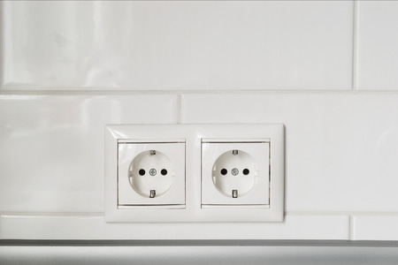 Double white socket on white wall as a background photo