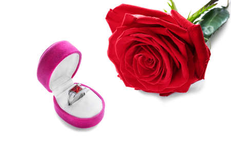 Ring in a box and red rose on white background photo