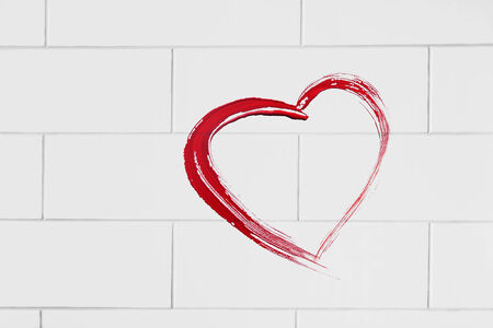 Red heart painted on white brick wall as a background photo
