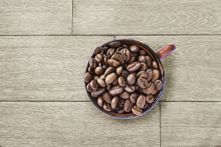 Cup full of coffee beans on wooden desk as a background photo