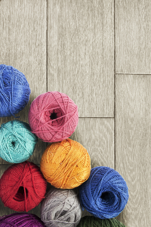 Group of multicolor yarn balls over wooden background photo