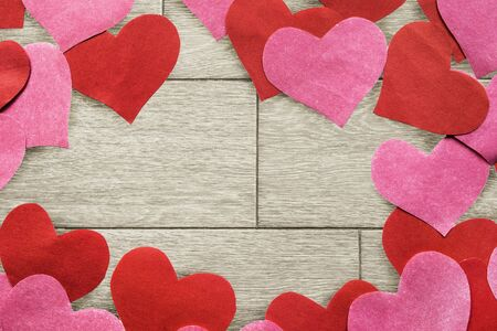 A lot of paper pink and red hearts over wooden background photo