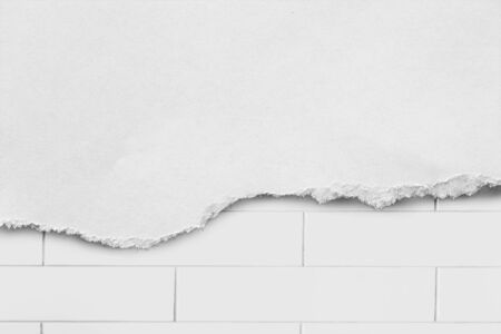 Torn white  paper over white brick wall as a background photo