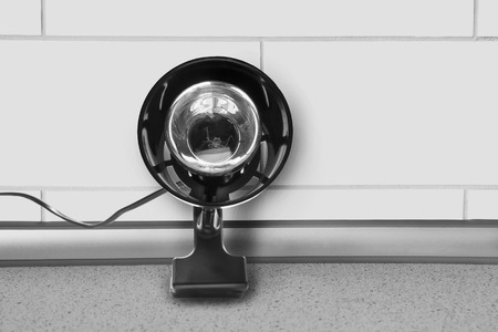 reading lamp: Reading lamp on a table against brick wall as a background Stock Photo