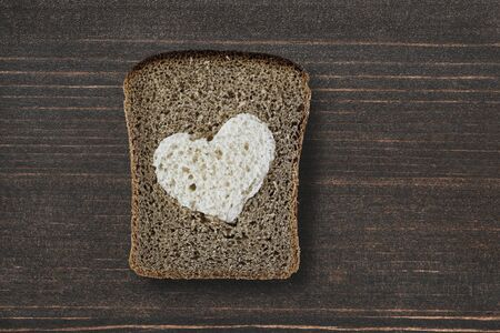 Piece of rye bread with a white heart silhouette on wooden desk photo