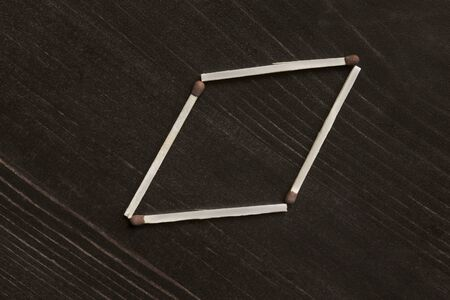 rhomb: Safety matches in the shape of rhomb on wooden background