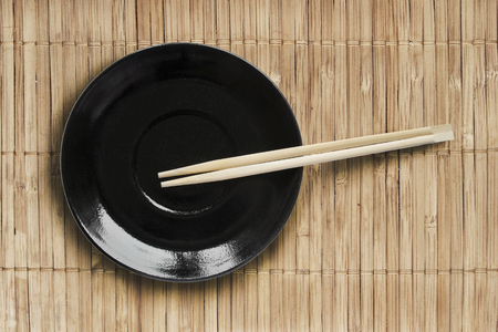 Black plate and wooden chopsticks on bamboo mat as a background photo