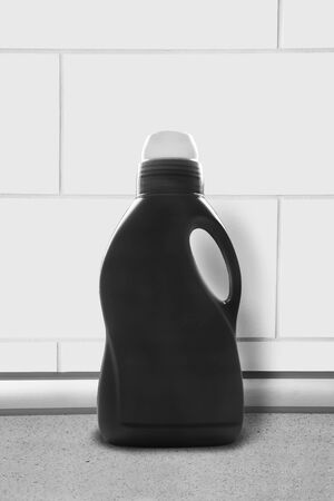 a jar stand: Black household chemistry bottle against white brick wall
