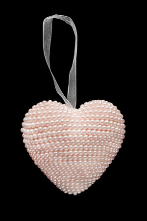 pink pearl: Pink pearl heart on white ribbon isolated over black