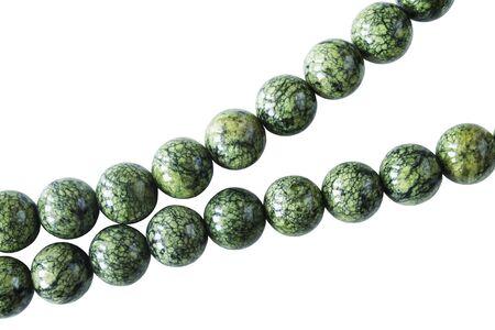 jasper: Strings of green jasper beads on white background