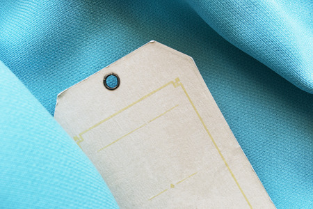 Blank carton label on blue silk as a background photo
