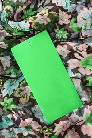 Green blank label on draped silk as a background photo