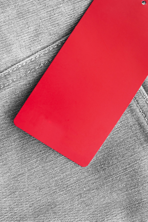 Red blank label on gray denim as a background photo