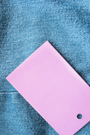 Pink blank label on blue denim as a background photo