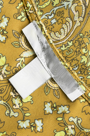 docket: Blank label on yellow ornamental silk as a background