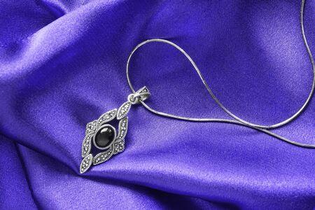 draped: Obsidian silver pendant on purple draped satin