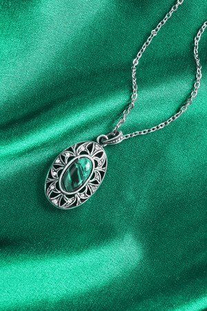 Turquoise silver pendant on blue silk as a background Archivio Fotografico