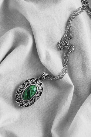 malachite: Vintage malachite pendant on white draped linen Stock Photo