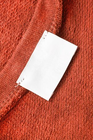 docket: Blank white clothes label on terracotta cloth as a background