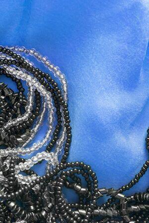 blue satin: Black beads on blue satin as a background Stock Photo