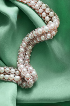 pink pearl: String of pink pearl on green silk as a background Stock Photo
