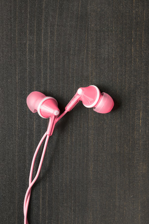handsfree telephones: Pink wired earphones on wooden background Stock Photo