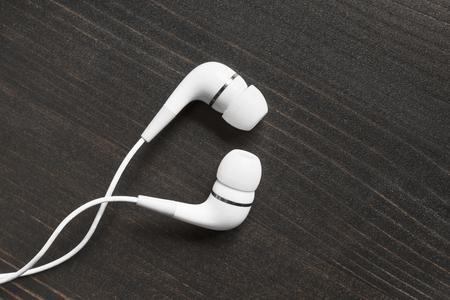 handsfree telephones: White wired earphones on wooden background Stock Photo