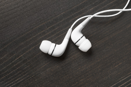 wired: White wired earphones on wooden background Stock Photo