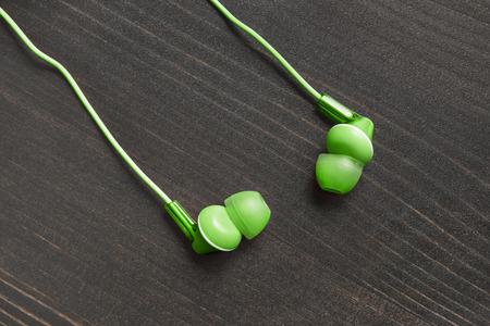 handsfree telephones: Green wired earphones on wooden background