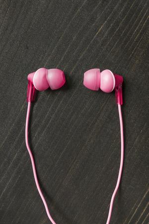 handsfree telephones: Pink wired earphones on wooden background Stock Photo
