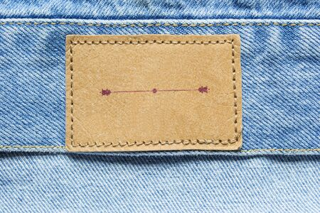 docket: Blank brown label on blue denim as a background