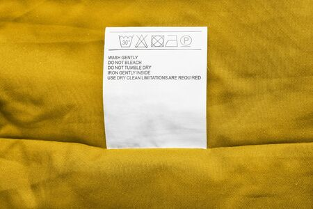 blank tag: Washing instructions label on yellow cloth as a background