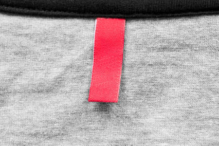 knitwear: Blank red clothes label on gray knitwear as a background