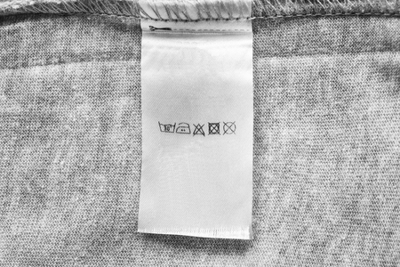 Washing instructions label on gray cloth as a background
