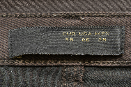 docket: Black clothes size label on brown denim