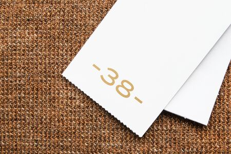 38: White blank 38 size label on brown knitwear Stock Photo