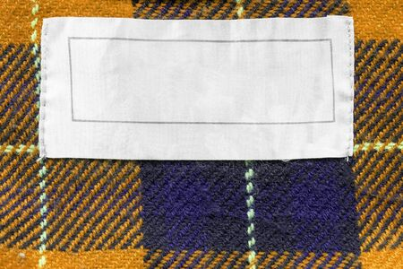 blank tag: Blank white label on yellow plaid as a background