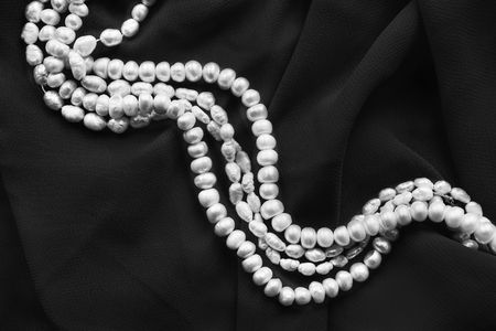 black silk: Strings of white pearl on black silk as a background