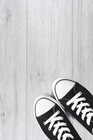lacing sneakers: Pair of black gumshoes on white wooden floor
