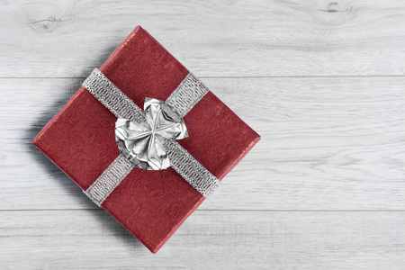 Red gift box with silver bow on wooden background